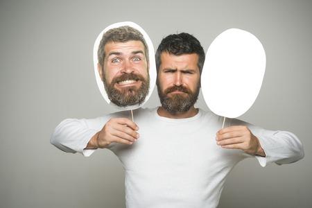 感情と感情灰色の背景に男やあごひげの男。驚きと深刻な顔を持つヒップスターは、肖像画のネームプレートを保持します。床屋のファッションと 写真素材