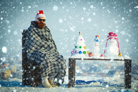 snow christmas new year concept Hipster in plaid blanket sitting on chair on winter day. Man in red santa hat and glasses. Snowmen and snow xmas tree on wooden table. Christmas and new year.