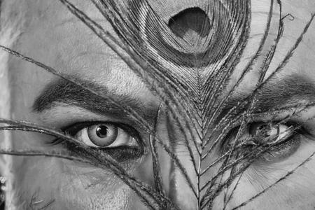 menselijke ogen met blauwe groene kleur lens op gezicht met prachtige pauwenveer wenkbrauw als halloween of carnaval vakantie kostuum, close-up