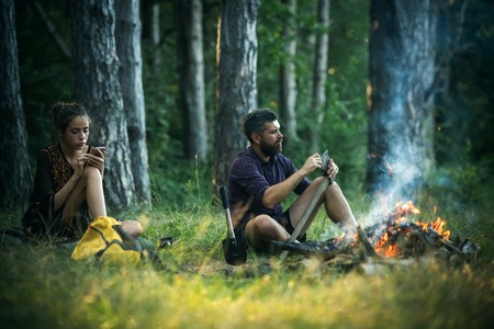 Girl or woman use mobile phone. Man hipster sharpen axe. New technology or archaism concept. Camping, hiking, summer vacation. Couple of hikers relax at bonfire in forest. Stock Photo