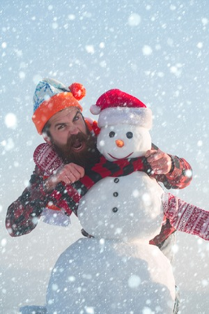 new year christmas snow concept New year guy, happiness. xmas leisure and winter season. Snowman, winter holiday celebration. Santa claus man with snowman in hat. Christmas man with beard on happy
