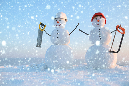 new year christmas snow concept Christmas or xmas decoration. New year snowman from snow with saw. Building and repair work. Happy holiday and celebration. Snowman builder in winter in helmet.