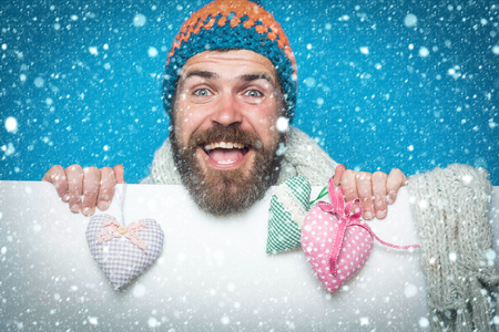 new year christmas snow concept Holiday celebration and party. Hipster with heart on blue white background. Valentines day and love. Guy with happy face in winter hat and scarf. Man with long beard Stok Fotoğraf