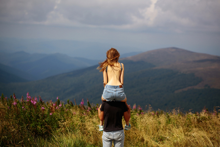 Romantic couple of pretty naked girl with bare back and handsome man in love embrace on cliff on summer day over mountain tops and sky Stockfoto