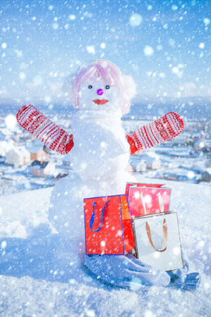 new year christmas snow concept new year or christmas snowman in pink wig, and mittens with present pack or shopping bag in winter outdoor Stock Photo