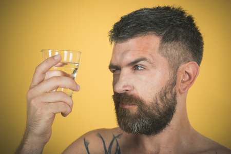 Man with long beard hold water glass on yellow background. Health and dieting. Life source and healthcare. Hangover and thirst. Hipster drink clean healthy water, refreshing. Imagens - 91533519