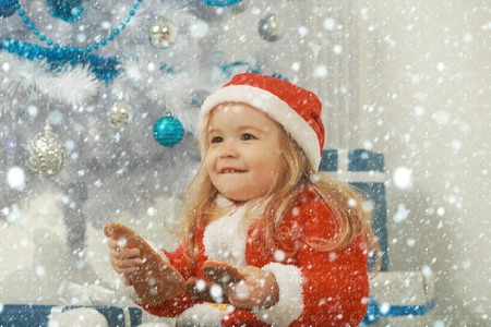 new year christmas snow concept New year small boy at Christmas tree. Winter holiday and vacation. Xmas party celebration. Santa claus kid with present box, black Friday. Christmas happy child with