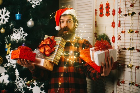 Winter holiday and xmas. santa claus man at decoration and garland. Christmas man with beard on face and garland. Party and celebration. New year guy with illuminated wire , present box and toy.