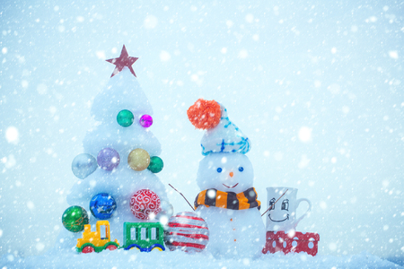new year christmas snow concept Christmas tree with decorations, toy train, cup and present box. xmas and new year. Winter holidays concept. Snow sculptures on blue background. Snowman with smiley