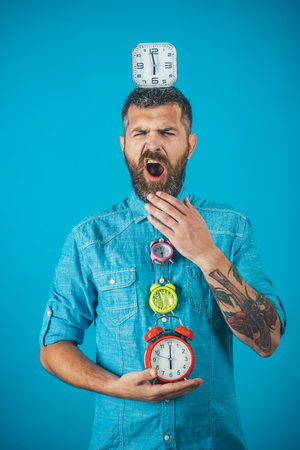 sleepy man yawn with beard hold alarm clock. Time management and countdown. Lifetime, business and deadline. Overtime and urgency. Time and perfect morning.