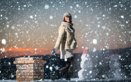 snow christmas new year concept xmas leisure and winter activity. Snowman, winter holiday celebration. Santa claus girl with snowman at chimney. New year woman outdoor. Christmas woman with happy face