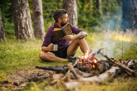 Summer vacation, activity. Man traveler read and drink at campfire flame. Camping, hiking, lifestyle. Hipster hiker with book and mug at bonfire in forest. Sustainable education, environment concept. Stock Photo
