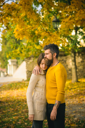 Love relationship and romance. Man and woman at yellow tree leaves. Couple in love in autumn park. Autumn happy couple of girl and man outdoor. Nature season and fall holiday. Stock Photo