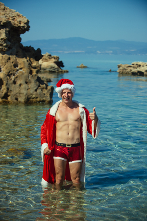 Christmas happy man in water show thumb up. Santa claus muscular guy in red Christmas costume. Winter holiday vacation. Xmas party celebration. New year man swim at beach.
