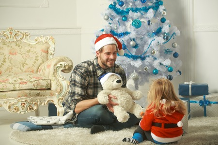 Christmas happy child and father with bear on white background. Santa claus kid and bearded man at Christmas tree. Winter holiday. Xmas party celebration, fathers day. New year small boy son and man.
