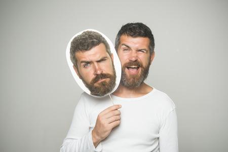 床屋のファッションと美しさ。ウインクと深刻な顔を持つヒップスターは、肖像画のネームプレートを保持します。灰色の背景に男やあごひげの男