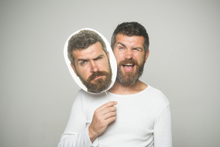 Barber fashion and beauty. Hipster with winking and serious face hold portrait nameplate. Guy or bearded man on grey background. Feeling and emotions. Man with long beard and mustache. Imagens