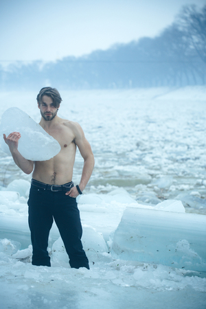 Cracked ice at Hercules guy in Christmas. Man with bare muscular chest hold big ice block. Power and strength of man with frozen hummock. Winter holiday and activity. Cold weather and ice age.