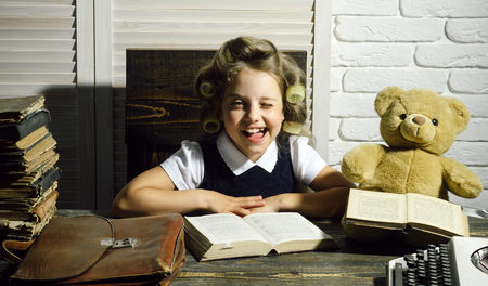 Little baby secretary in cabinet with bear. Child with briefcase and typewriter on table. Education and childhood. Kid choose career of journalist or writer. Small girl with curler in hair read book.