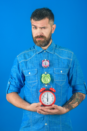 Man with beard hold alarm clock. Time and perfect morning. Time management and countdown. Overtime and urgency. Lifetime, business and deadline, watchmaker Stock Photo