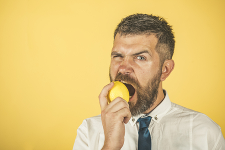 Vegetarian, health and wellbeing. Dieting and fitness. Vitamin citrus at hipster on yellow background. Man with long beard eat lemon. Fruit and healthy organic food, copy space Imagens