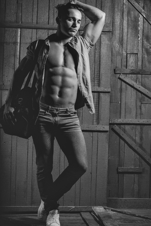 Handsome fashionable sexy sensual muscular young macho man with bare torso and stylish hair in jeans shirt holding sport bag indoor standing on wooden background, vertical picture