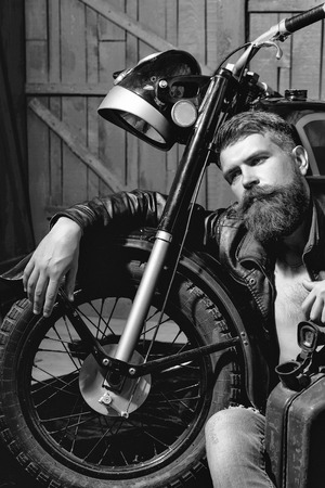 Bearded man hipster biker brutal male with beard and moustache in leather jacket sits near motorcycle with rusty metallic gas can on wooden background