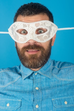man with beard in white mask on blue background, homosexual and fetish, gay and lgbt, holiday party and carnival