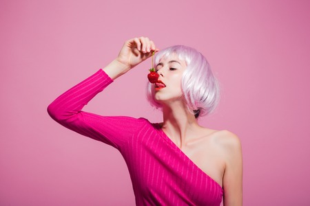 フルーツとビタミン人工髪の女の子は口の中に赤いベリーを保持します。スキンケア、スパ、健康。美しさとファッション。かつらの女性はピンク 写真素材