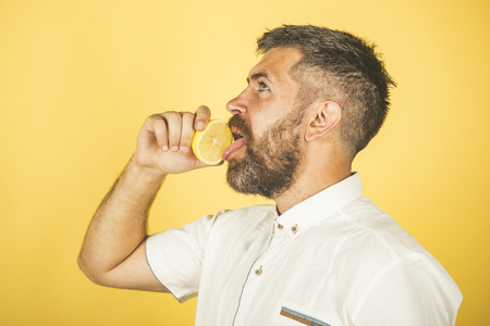Vegetarian, health and wellbeing. Fruit and healthy organic food. Vitamin citrus at hipster on yellow background. Dieting and fitness. Man with long beard lick lemon.
