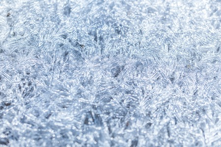 Texture of ice surface. Winter ice background, new year. Frost crystal border on ice, Christmas backdrop. Background with ice frozen texture. Christmas, frozen window texture.