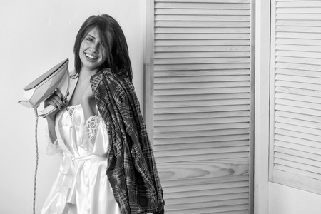 Happy pretty girl or beautiful woman, housewife, with long brunette hair in sexy dressing gown smiling with electric iron in hand for ironing clothes on white wall. Housework and housekeeping Foto de archivo