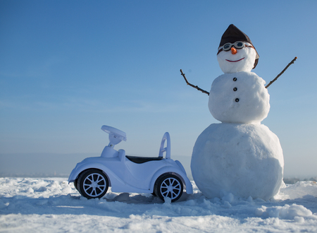 Snowman in winter with toy car, travel and vaction. Xmas or christmas decoration, aviation. New year snowman in pilot hat and glasses. Happy holiday celebration. Christmas and transportation.