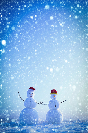 christmas new year snow concept christmas snowman couple in santa claus hat in winter at blue sky, copy space Stock Photo