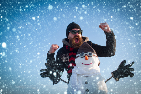 christmas new year snow concept New year guy at winter season. Snowman pilot, winter holiday celebration. Christmas man with beard on happy face. Santa claus man with snowman in hat. xmas