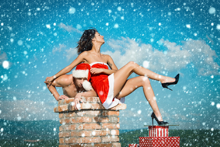 christmas new year snow concept Couple of man and girl on chimney. Christmas man and woman family. New year guy with muscular body on blue sky. Xmas red present box.