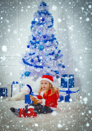 christmas new year snow concept Xmas party celebration. Santa claus kid with present box, black Friday. Winter holiday and vacation. New year small boy at Christmas tree. Christmas happy child bear Stock Photo