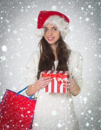 new year christmas snow concept New year girl with present shopping bag, black friday. Santa claus girl with gift. Boxing day and christmas sale. Xmas party and holiday celebration.