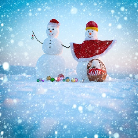 christmas new year snow concept Santa claus hat in winter. Christmas or xmas decoration toy. New year snowmen from snow in santa hat. Happy holiday and celebration. Snowman couple with present box
