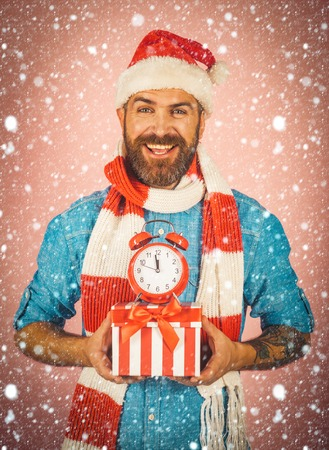 christmas new year snow Christmas man hold alarm clock and gift box. Hipster in santa hat, scarf smile on pink background. New year, xmas holidays celebration. Boxing day concept. Time to celebrate.