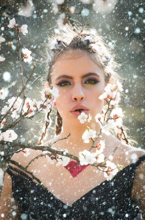 christmas new year snow concept woman in beautiful spring flower blossom in garden with fashion makeup on summer natural background, youth and health