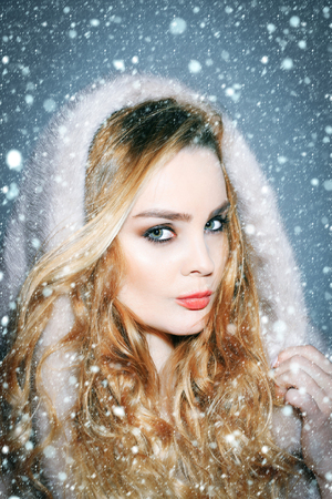 christmas new year snow Fashion, style, winter clothing concept. Woman in mink fur coat and hood on head. Girl with makeup face and long blond hair, hairstyle.