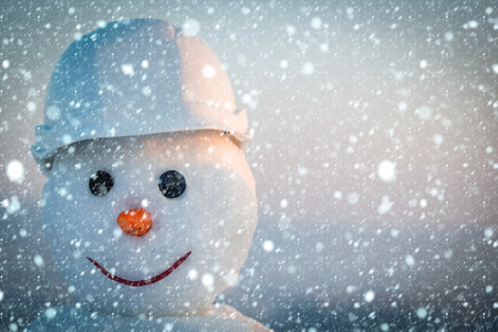 christmas new year snow concept New year snowman from snow in winter. Snowman builder in helmet. Happy holiday and celebration. Christmas or xmas decoration. Building and repair work., copy space 스톡 콘텐츠
