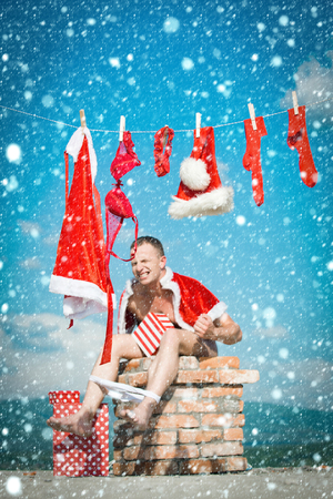 christmas new year snow Bad santa claus at clothes for drying shit on chimney. Stock Photo