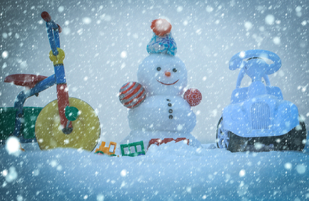new year christmas snow concept Tricycle, car and toys on snowy background. Christmas and new year. Holidays celebration concept. Festive surprise and presents. Snowman with smiley face on white sky.