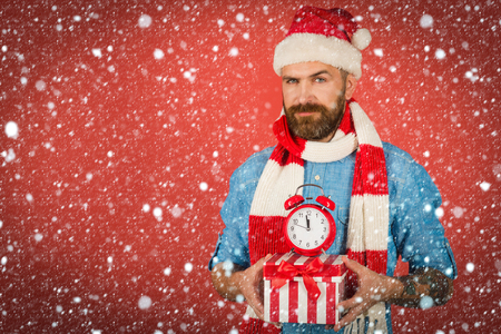 christmas new year snow concept Christmas man hold alarm clock and gift box. New year, xmas holidays celebration. Stock Photo