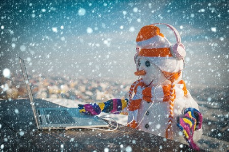 christmas new year snow concept Xmas or christmas decoration, audio book. Snowman in winter with laptop, headset and tea cup. Christmas and hot wine. Happy holiday celebration new technology. New year