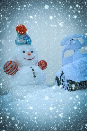 new year christmas snow concept Snowman and toy car on winter day on grey sky on snow background. Christmas and new year. Holidays celebration concept