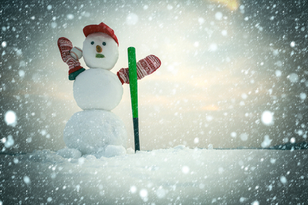 christmas new year snow concept New year snowman from snow in cap and mittens. Happy holiday and celebration. Winter activity, sport and fighting. Snowman with baseball bat. Christmas xmas decoration.