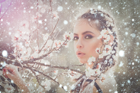 christmas new year snow concept cherry tree spring blossom, beautiful girl or woman portrait in flowers, young pretty female with fashion hair and makeup pose in blooming garden or summer park outdoor Stock Photo